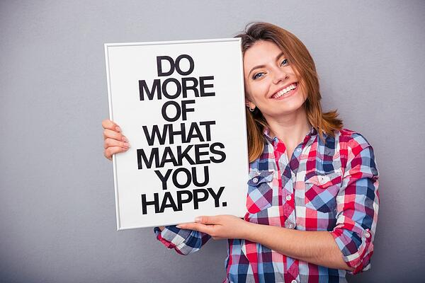 Happy woman in casual cloth holding board with motivational phrase over gray background