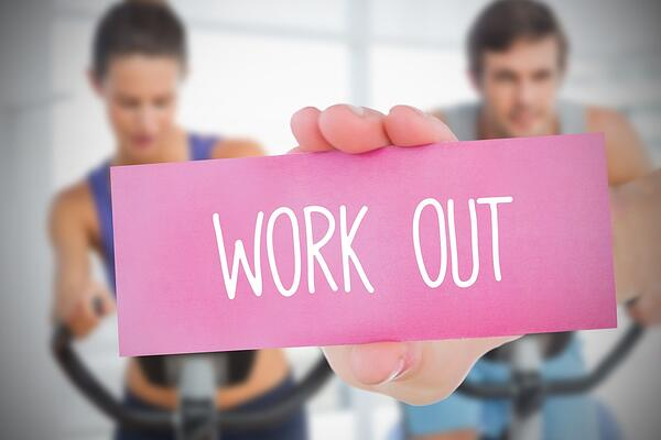Woman holding pink card saying work out against fitness class in gym