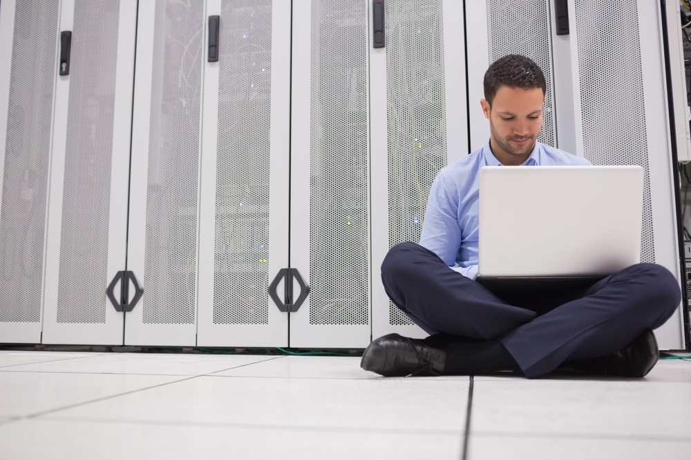 Technician sitting on floor working on laptop in data center.jpeg